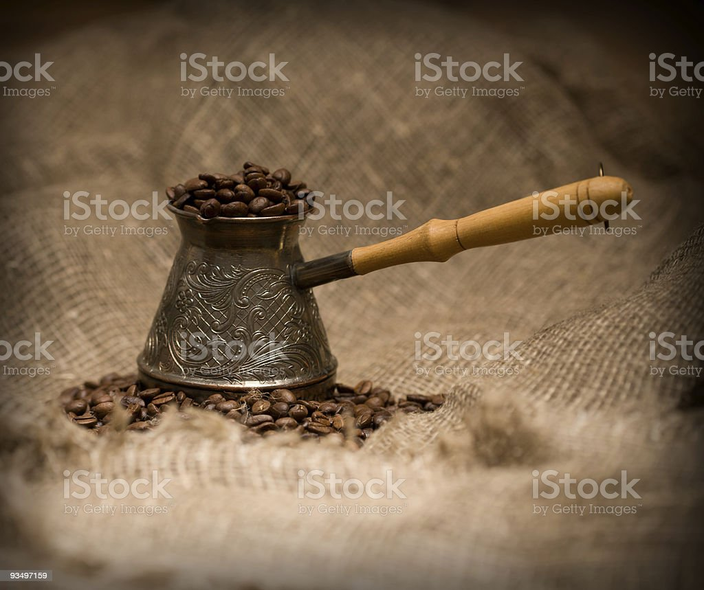 Cezve with freshly roasted coffee beans on sackcloth stock photo