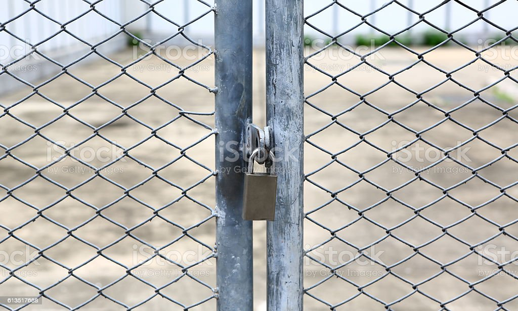chain link fence and metal door with lock stock photo