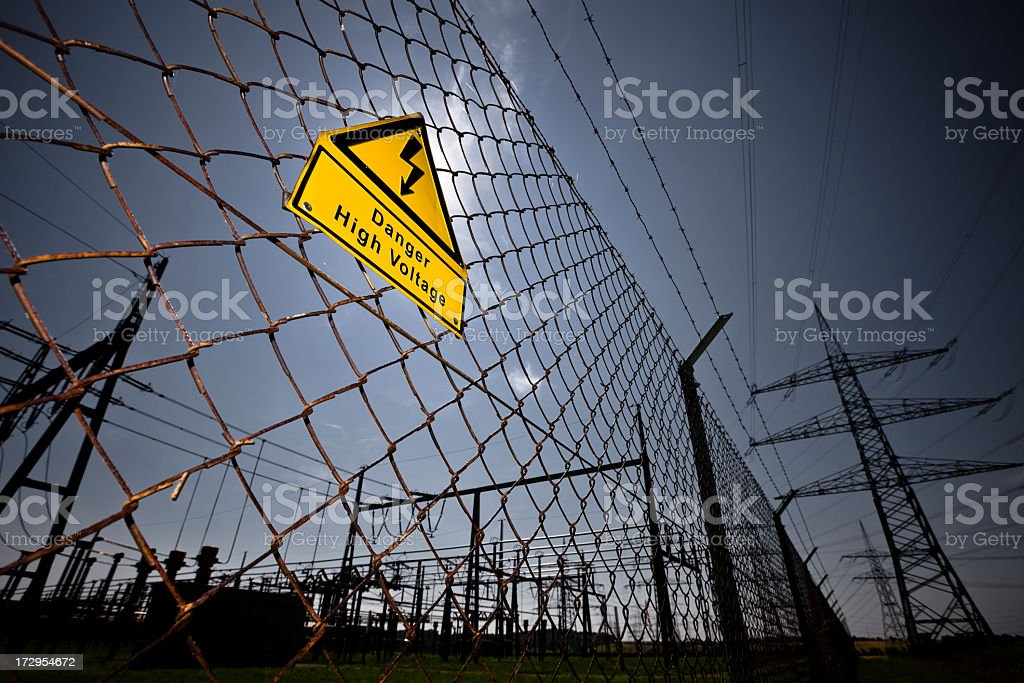 Chain link fence with a sign warning of high voltage stock photo