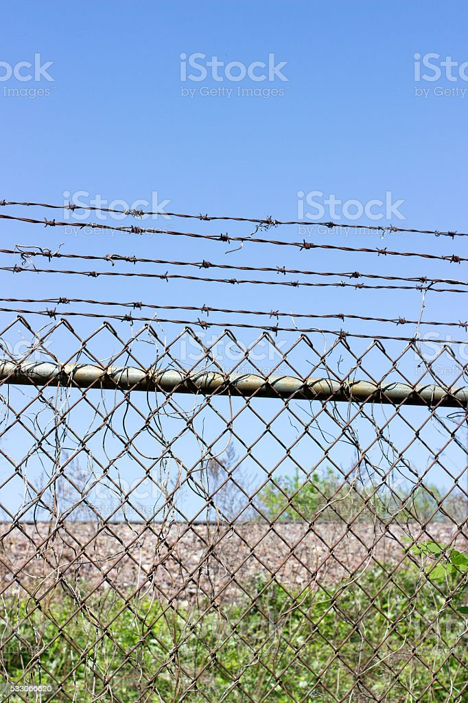 Chain link fence with barbed wire blue sky stock photo