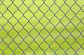 Chain link fence with green grass in background