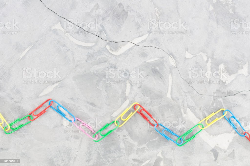 Chain of colored paper clips in the form of a zigzag on old gray cement stock photo