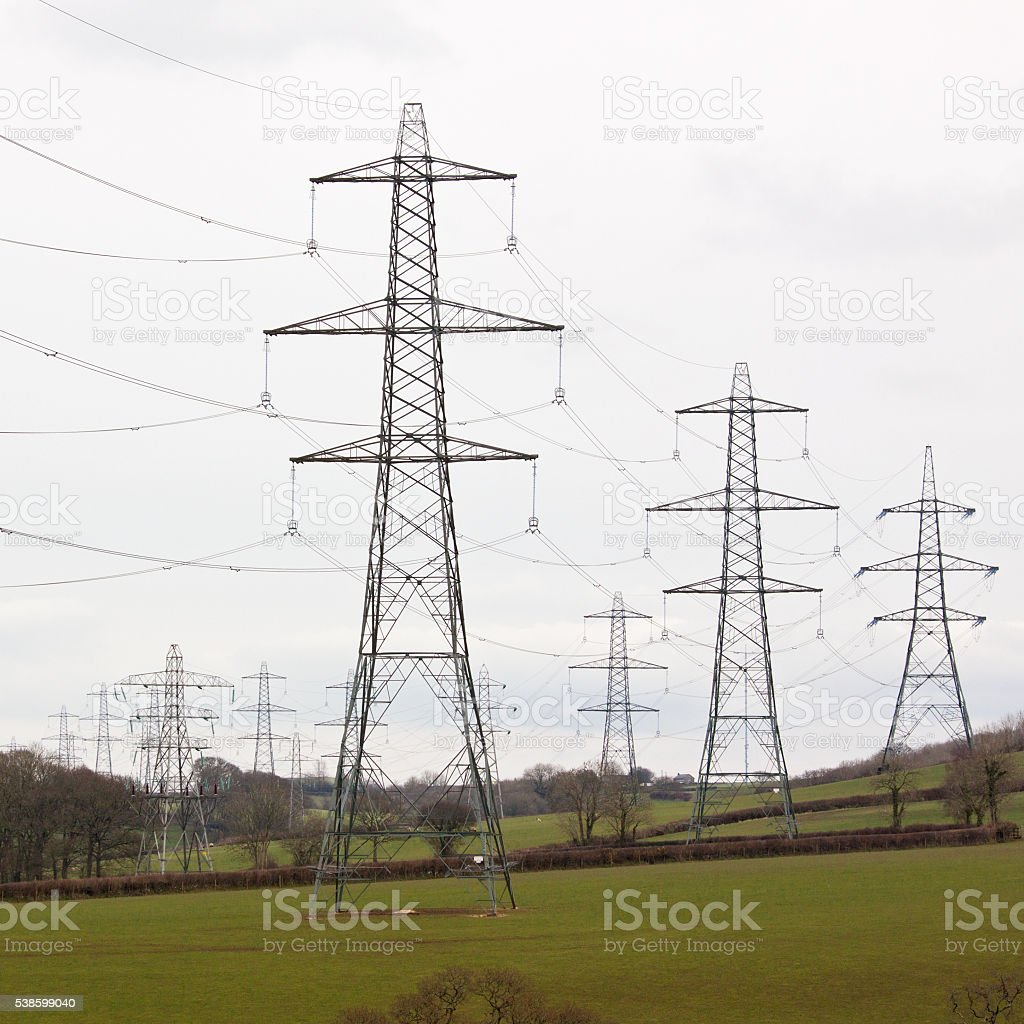 Chain of electricity pylons across agricultural land stock photo