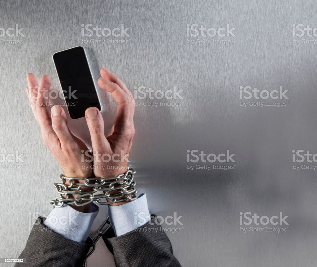 chain tied businessman hands grabbing corporate communication phone stock photo