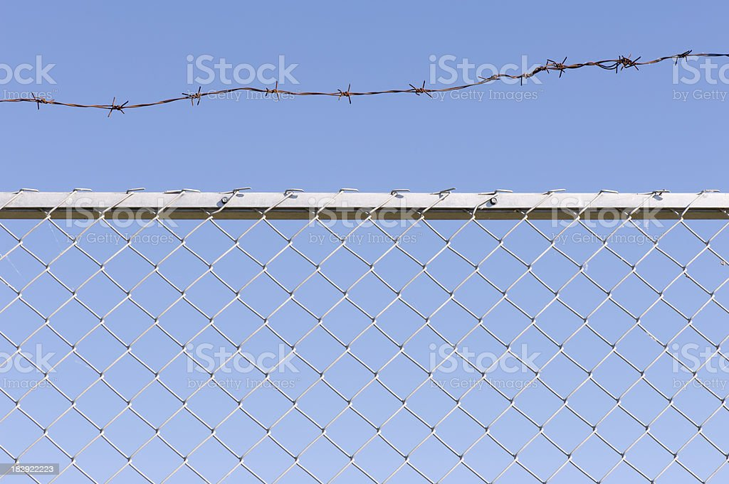 Chainlink fence and barbed wire royalty-free stock photo