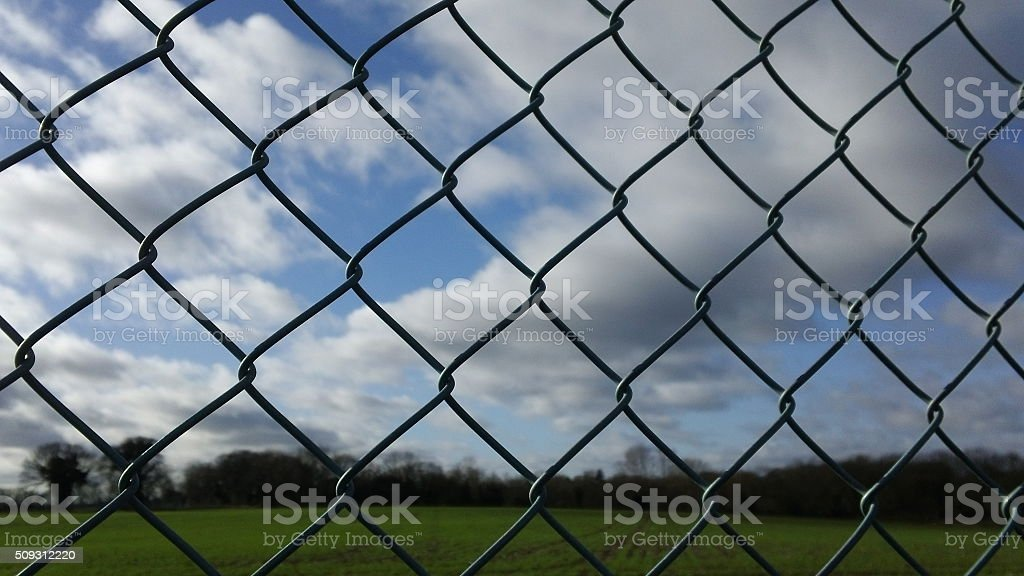 Chain-link fence, cloudy sky background stock photo