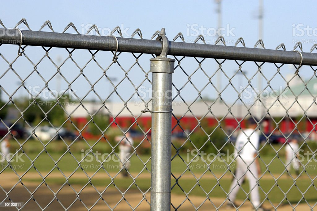 Chainlink fence surrounding baseball game stock photo