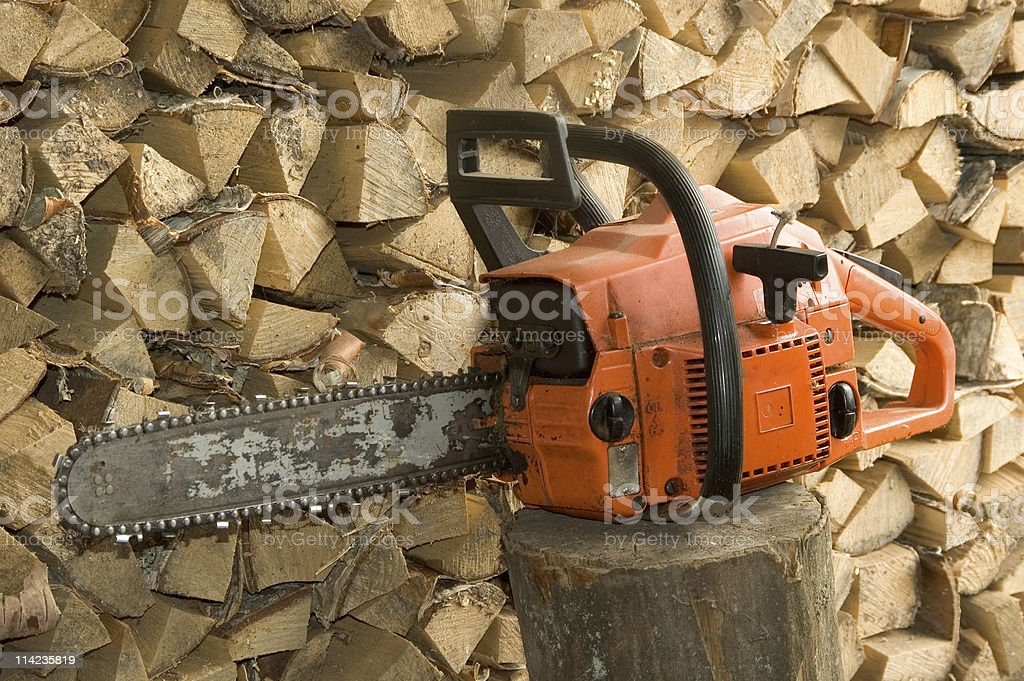 Chainsaw against firewood pile. royalty-free stock photo