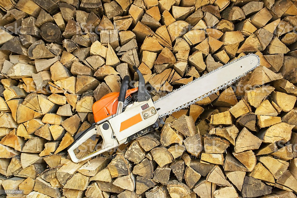 Chainsaw and Stacked Wood stock photo