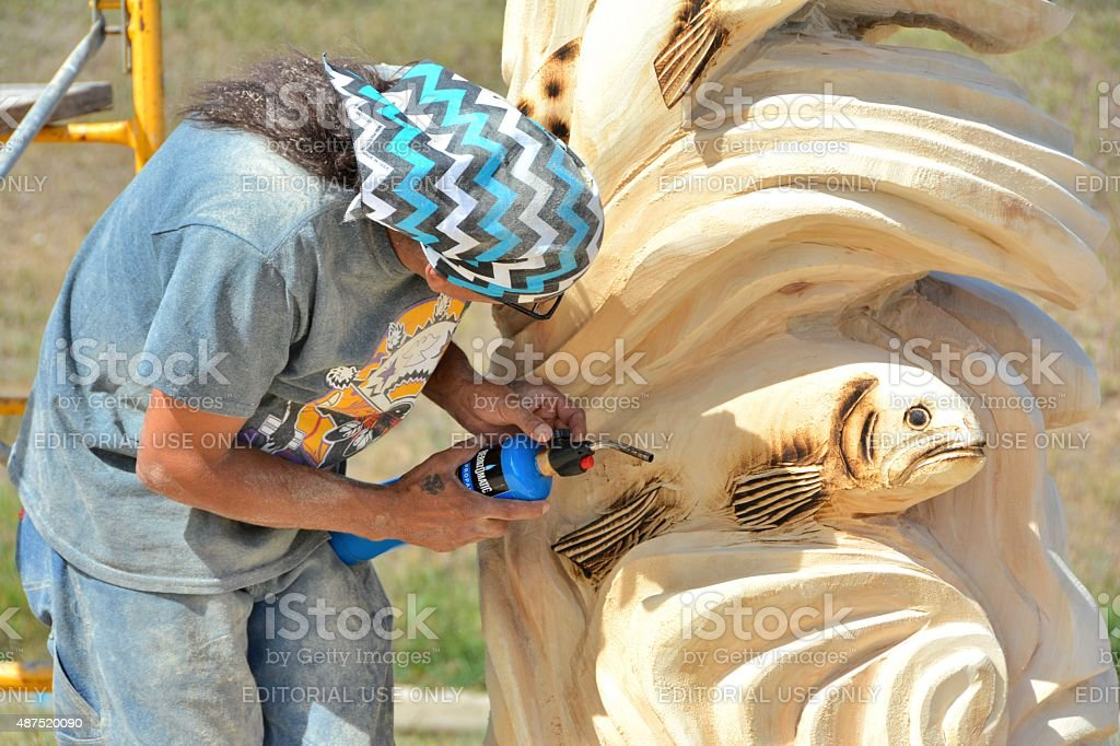 Chainsaw Carver working on his Sculpture stock photo