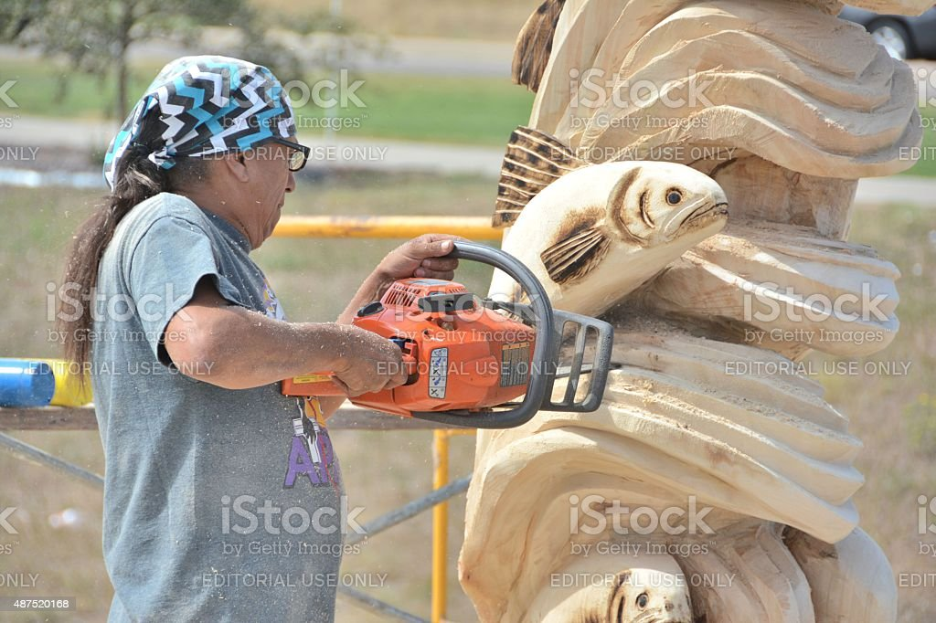 Chainsaw Competitor Carving his Sculpture stock photo