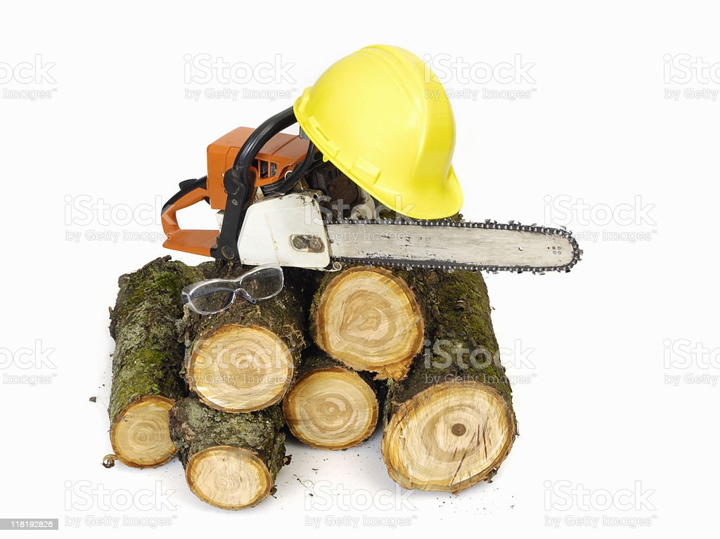 Chainsaw, logs and hardhat royalty-free stock photo