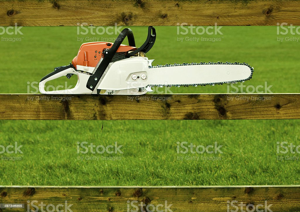 Chainsaw on a fence stock photo