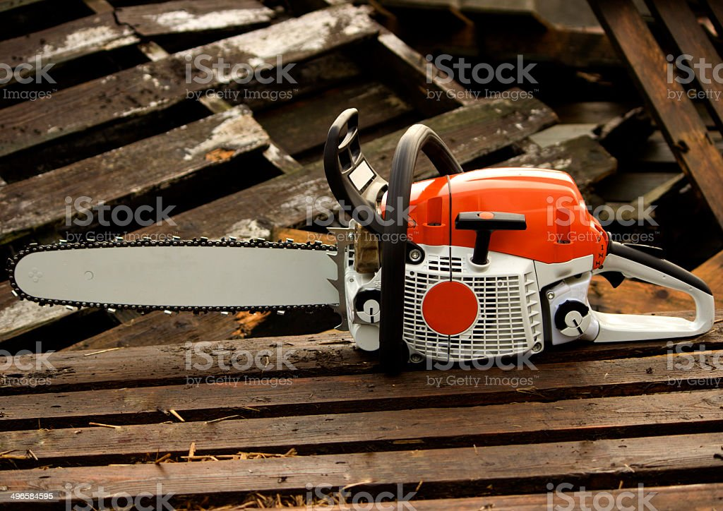 Chainsaw on a wooden palette stock photo