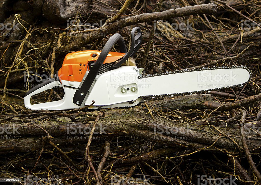 Chainsaw on fire wood stock photo