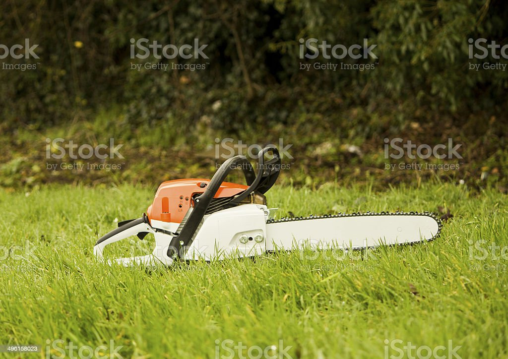Chainsaw on grass stock photo