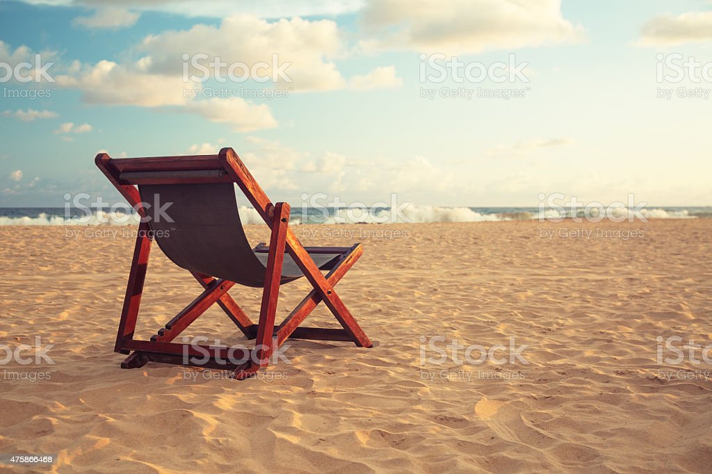 Chair at a topical beach in sunset stock photo