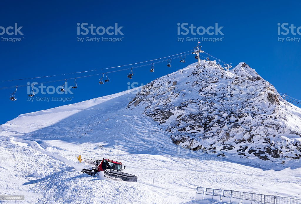 Chair lift and snow groomer in Alps stock photo