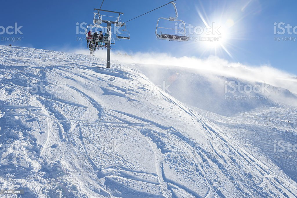 Chair Lift on a snowy mountain with a blue sky stock photo