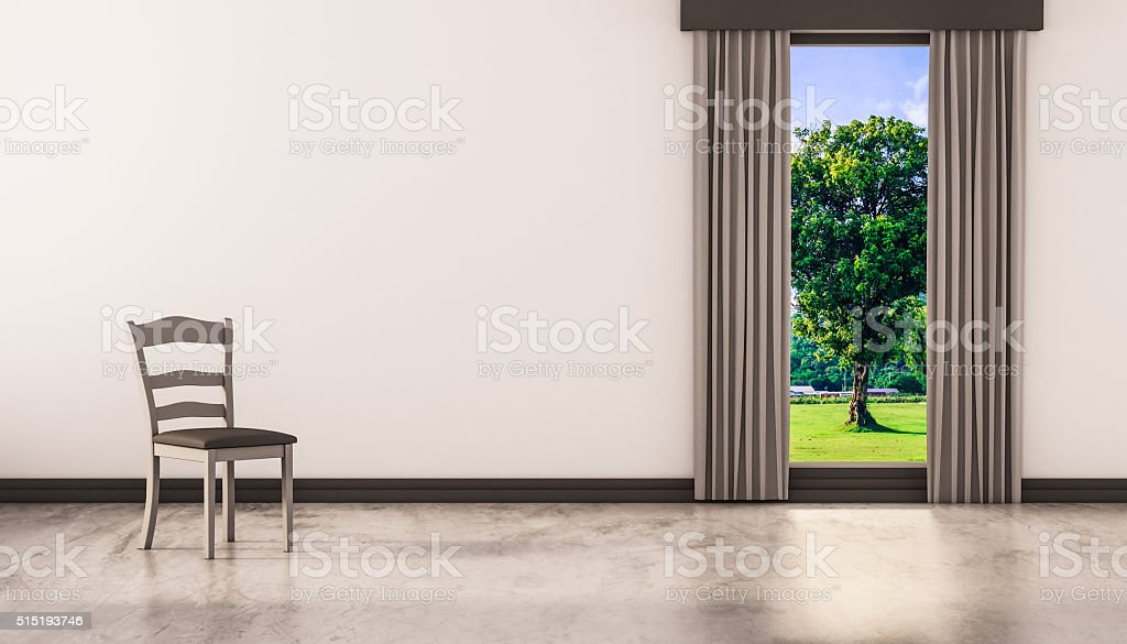 Chair on concrete polished floor with window and a tree stock photo