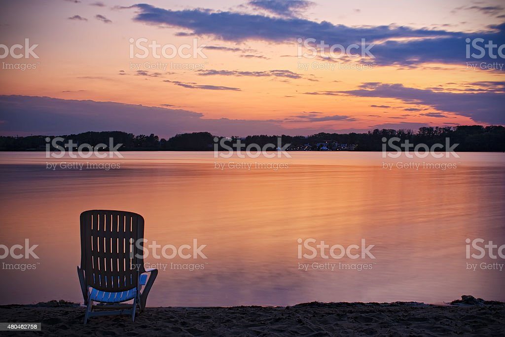 Chair on sand land coast near river water stock photo
