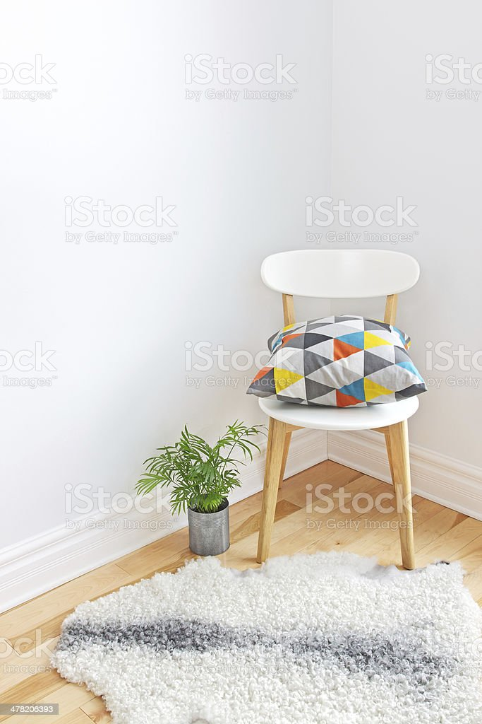 Chair with bright cushion and sheepskin rug on the floor stock photo