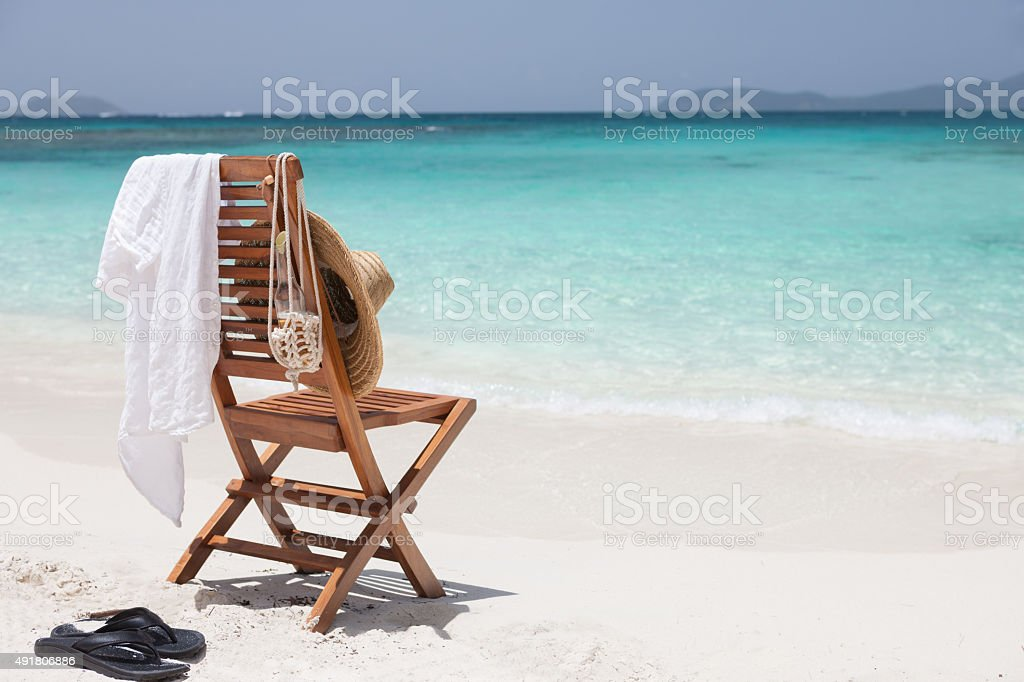 chair with hat, shirt, sandals and beer at a beach stock photo