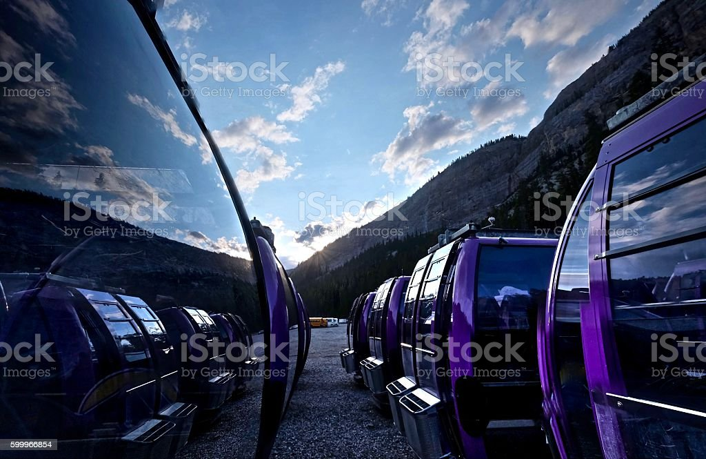 Chairlift cabins with sky and clouds reflection. stock photo