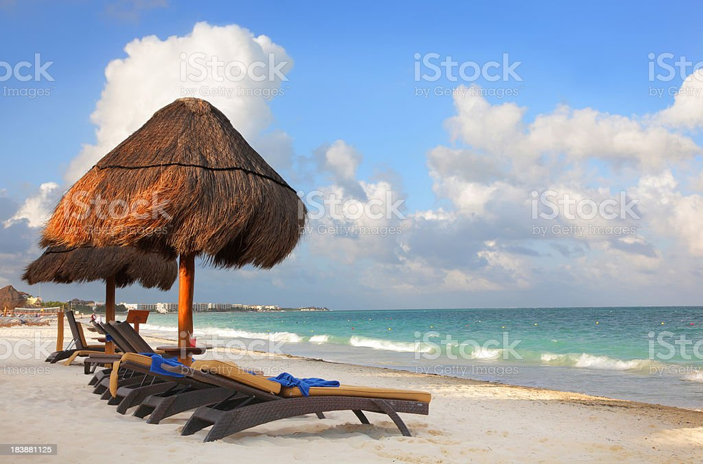 Chairs and palapas on a tropical beach stock photo