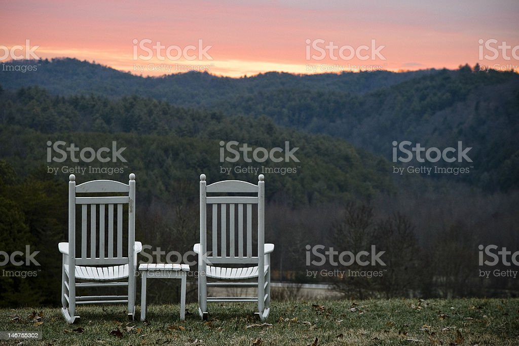 Chairs and Table Overlooking Hills at Sunset stock photo