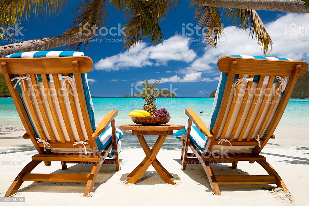 chairs and table with fruit at a tropical Caribbean beach stock photo