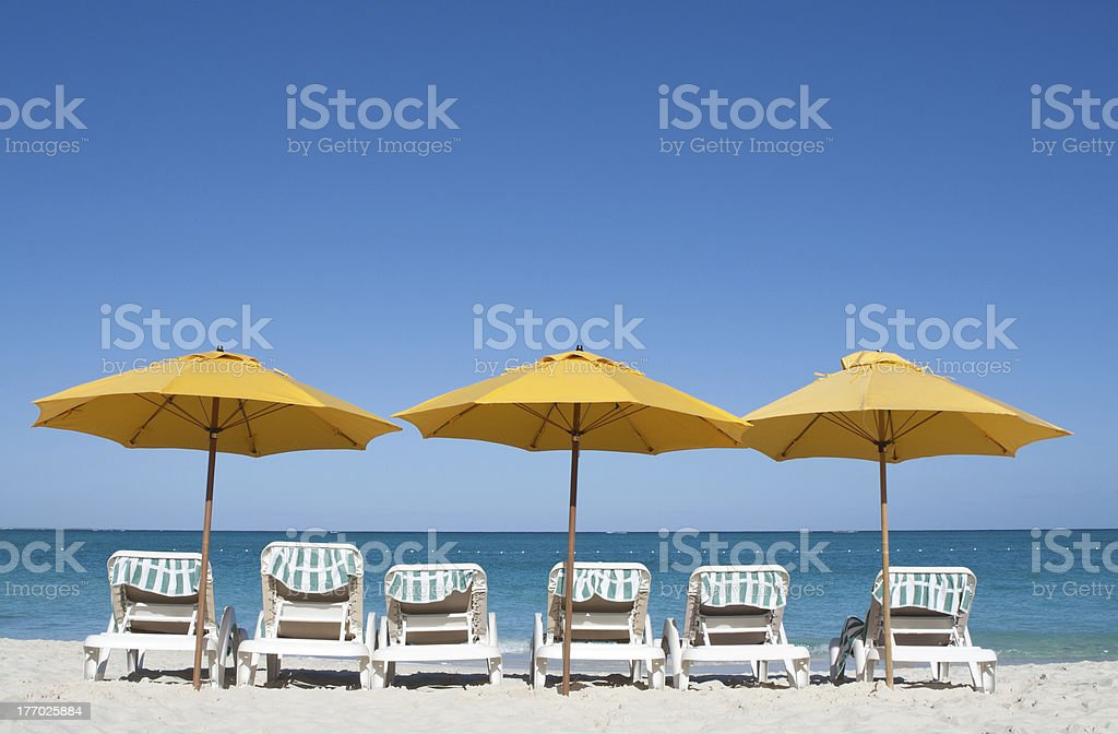Chairs and yellow umbrellas on Caribbean white sand beach stock photo