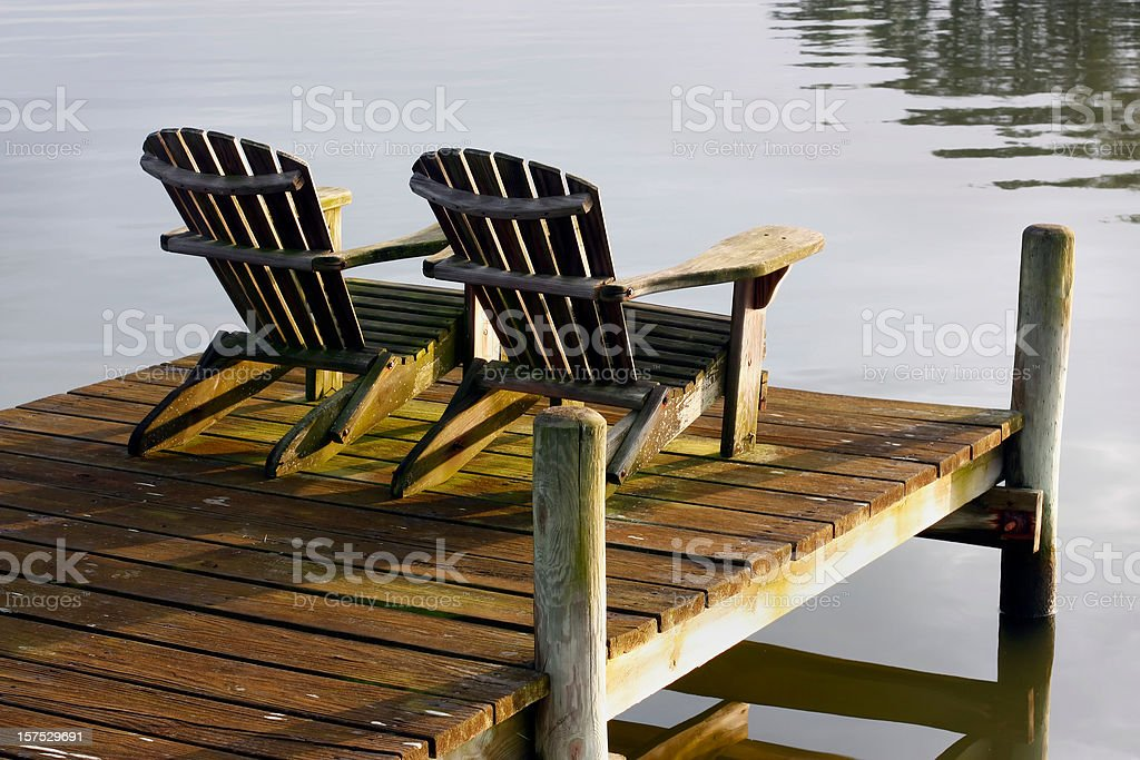 Chairs at sunset on bay stock photo