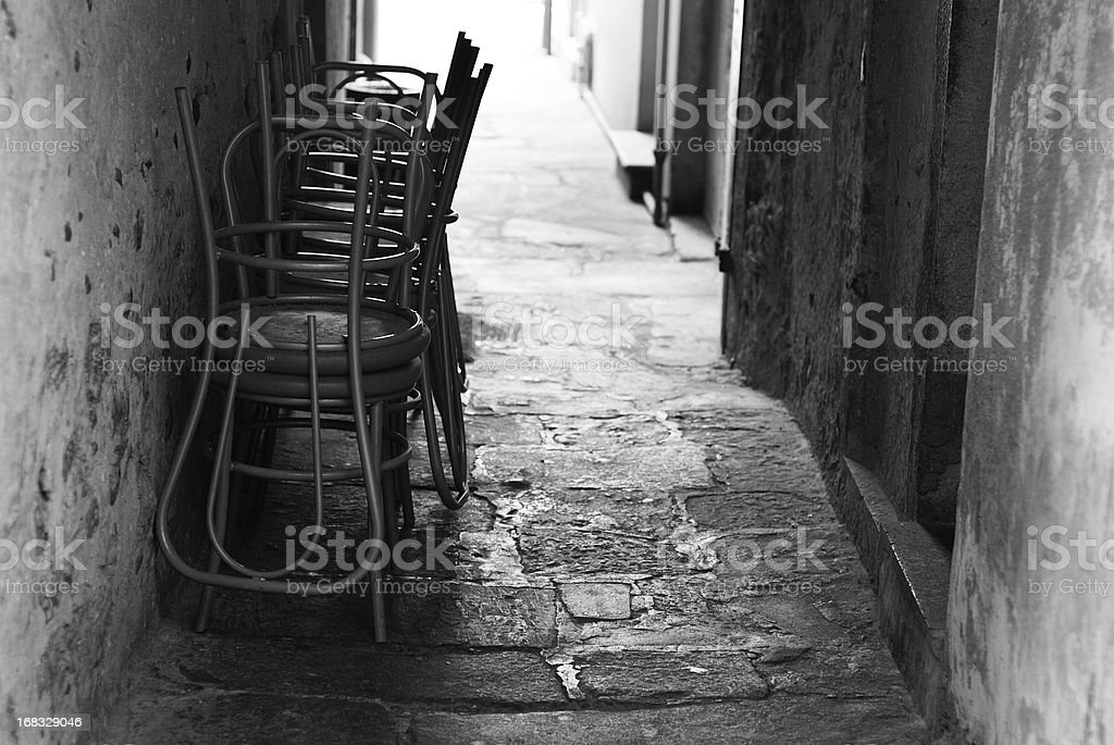Chairs back lit in narrow italian alley royalty-free stock photo