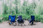 Chairs in front of campfire place in the forest