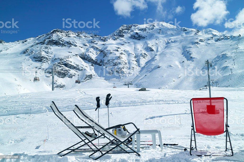 Chairs in snowy alpine French ski resort near ski chairlifts stock photo