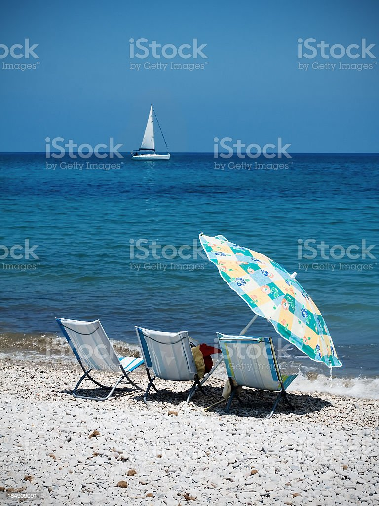 Chairs on a beach with ship in background stock photo