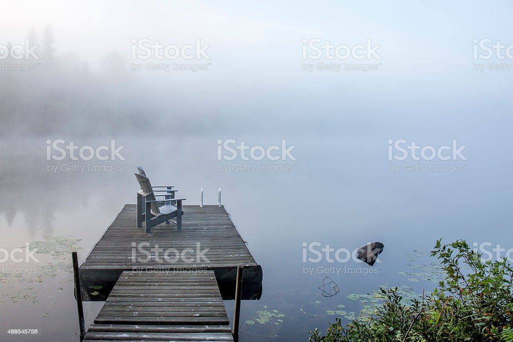 Chairs on a Dock Overlooking a Misty Lake stock photo