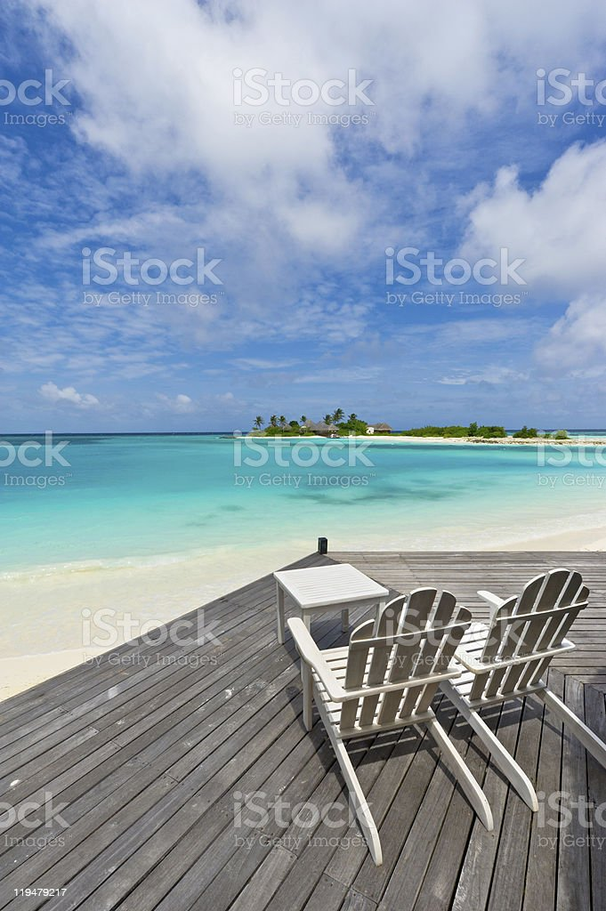 chairs on deck towards the sea in maldives resort royalty-free stock photo