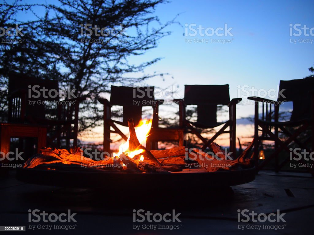 Chairs round a camp site fire at sunset stock photo