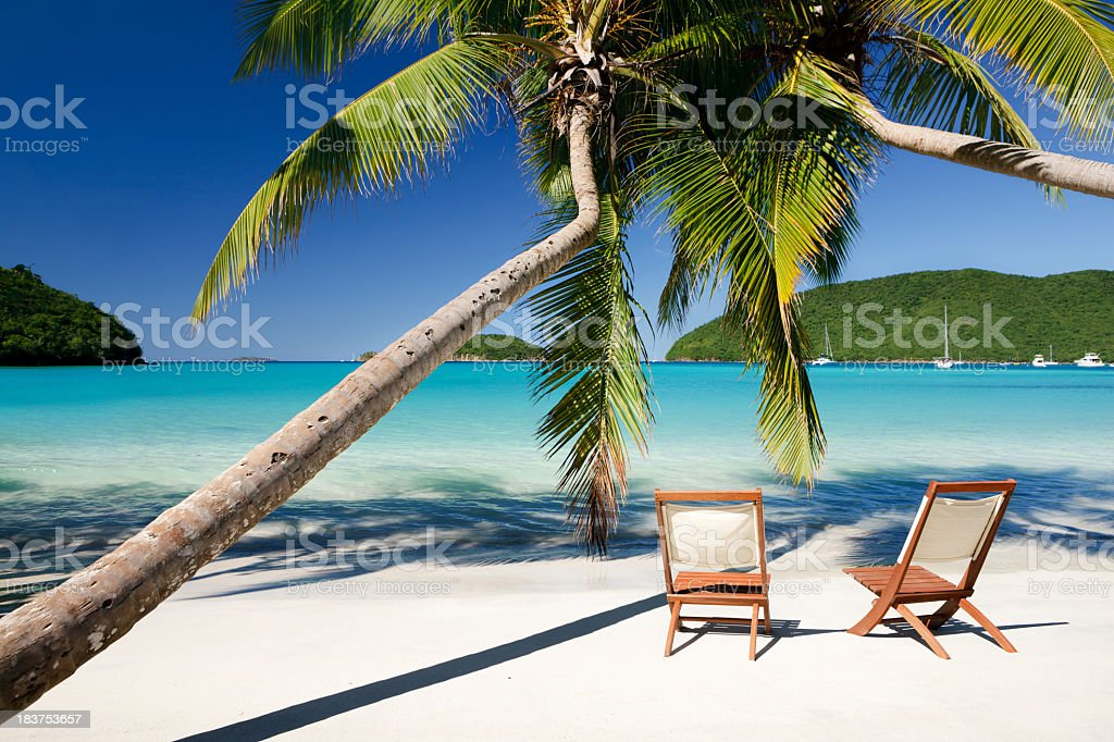 chairs under palm trees at a beach in Virgin Islands stock photo