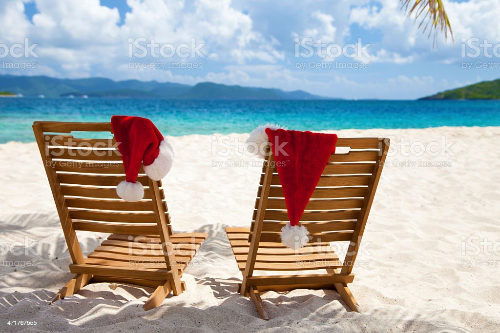chairs with Christmas hats under palm tree at a beach royalty-free stock photo