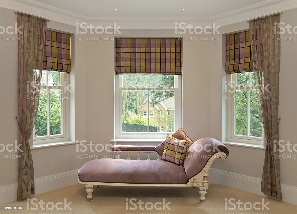 chaise longue in bay window stock photo