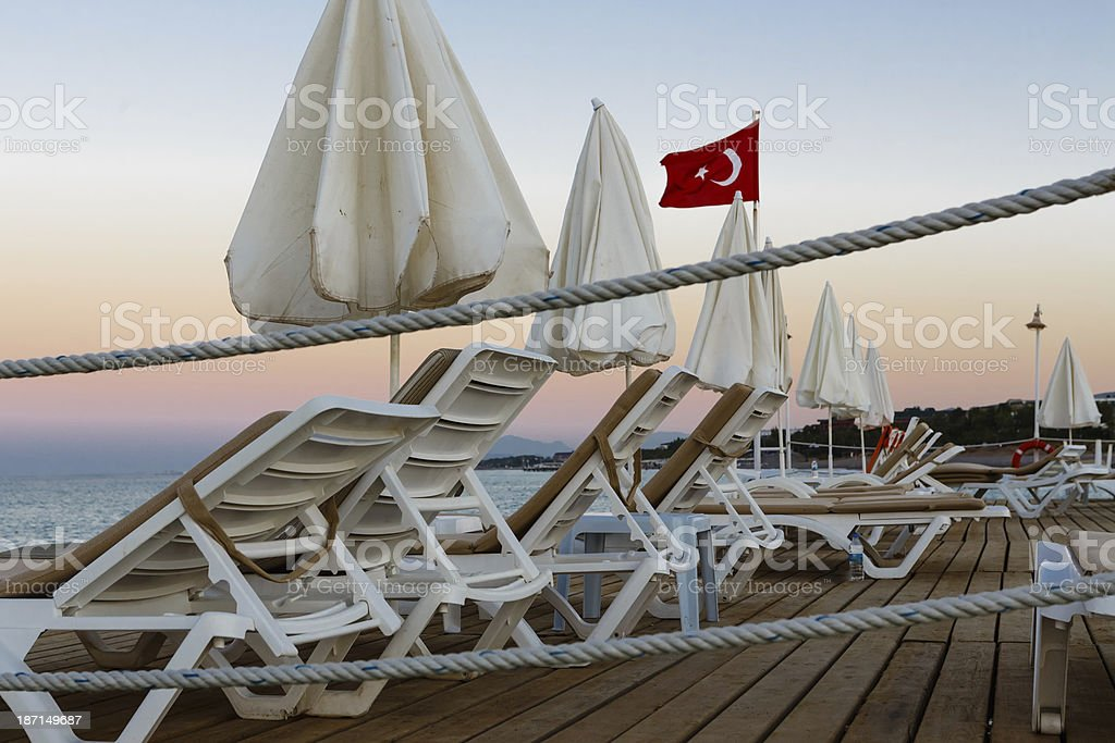 Chaise lounges and sun-protection umbrellas on a wooden pier stock photo