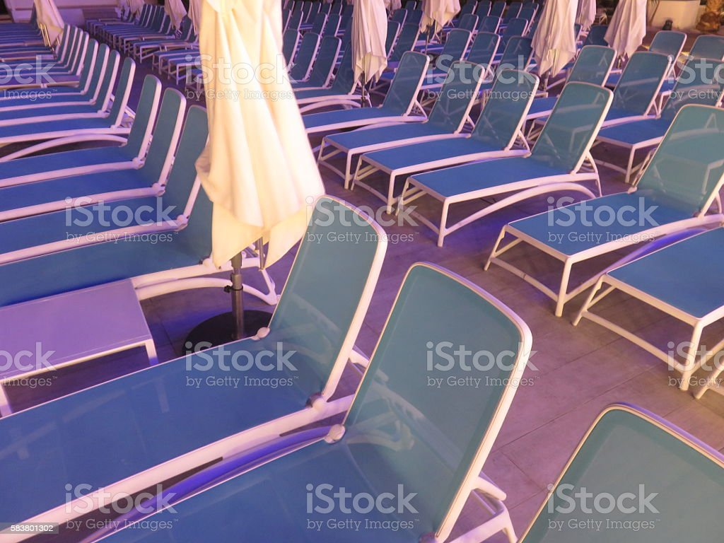Chaise-longues by the pool in the evening stock photo
