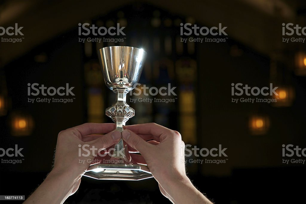 Chalice of Wine Lifted for Communion Blessing stock photo