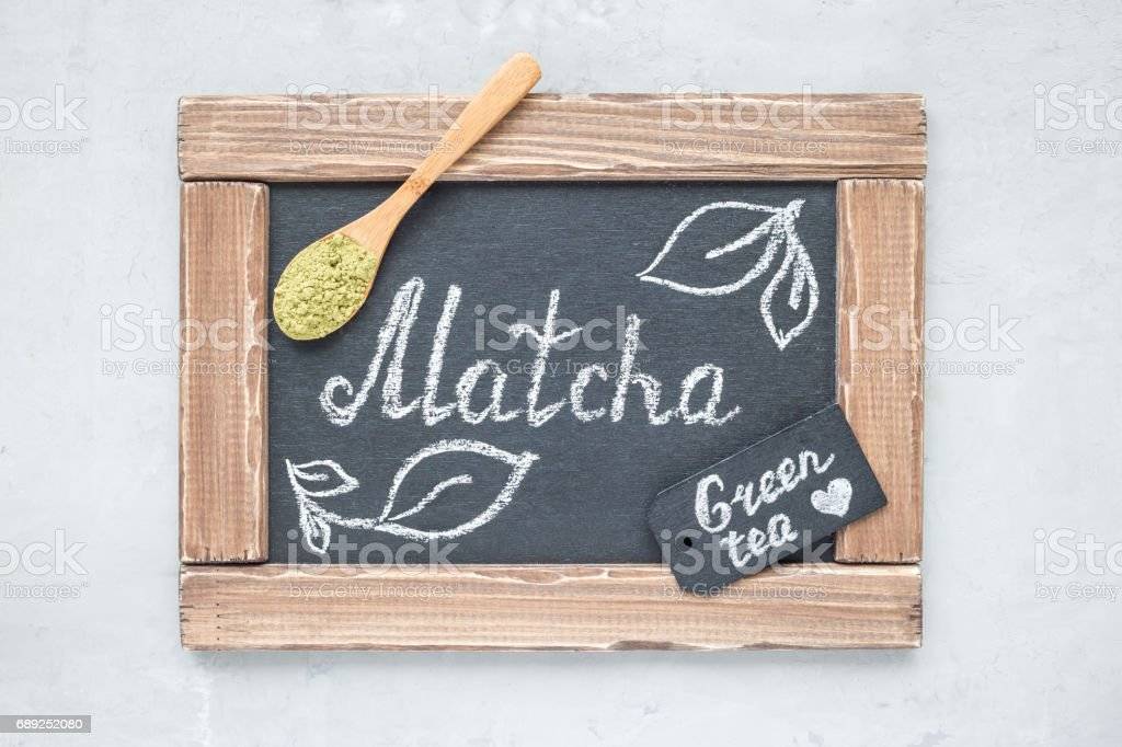 Chalk board with matcha lettering, green tea powder on background, top view, horizontal stock photo