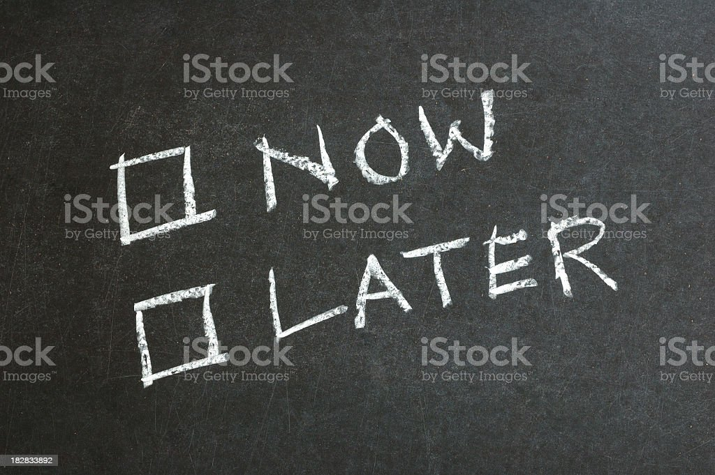 Chalk board writing for now and later with checkboxes stock photo