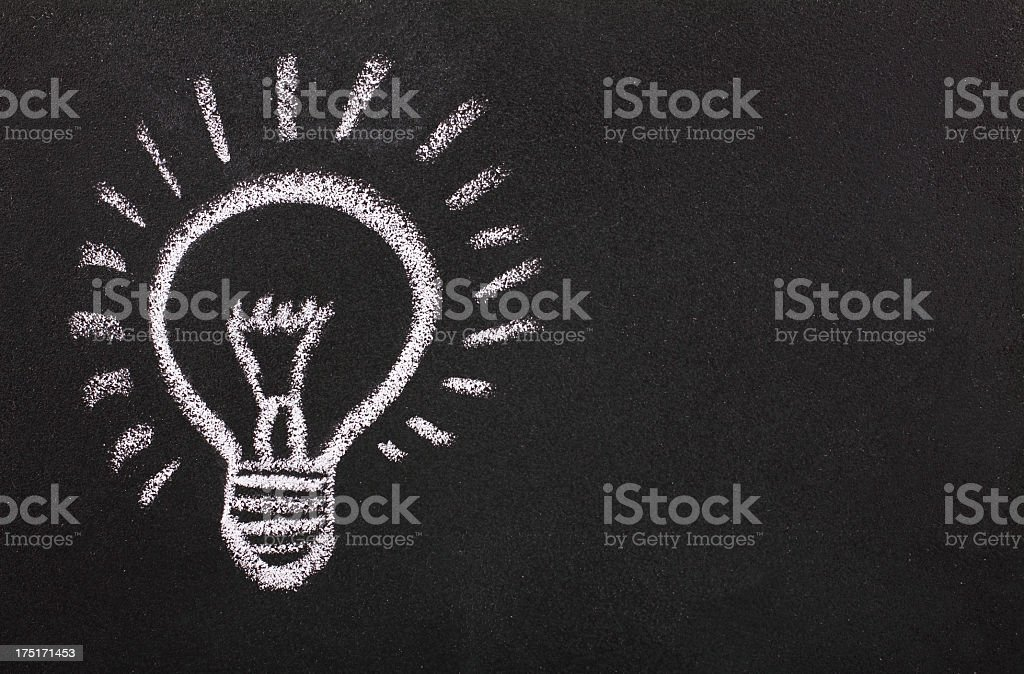A chalk drawing of a light bulb turned on stock photo