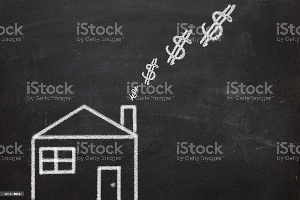 Chalk drawing of house burning money stock photo